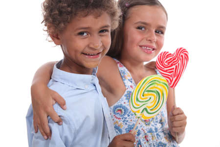 7 9 years: Two friendly kids eating colorful lollipops Stock Photo
