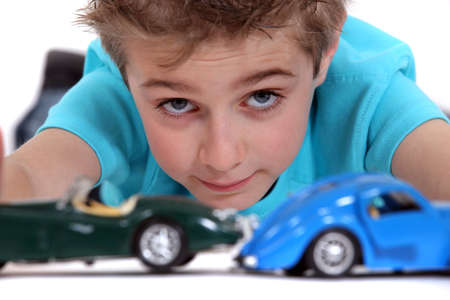 lying forward: Little boy playing with toy cars Stock Photo