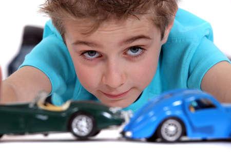transporte terrestre: Niño jugando con coches de juguete