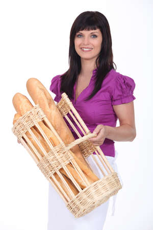 Woman with basket full of loaves of bread photo