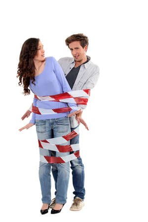 Couple being forcibly held together by caution tape Stock Photo - 13460085