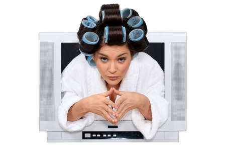 Woman with rollers in hair escaping from television photo