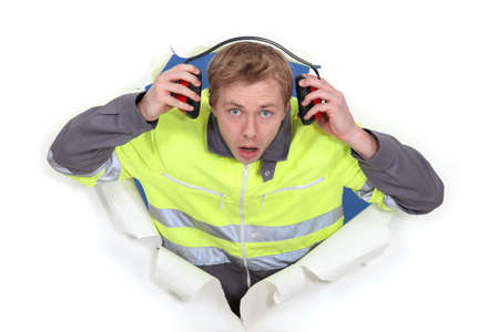 noise isolation: man with earmuffs emerging from poster Stock Photo