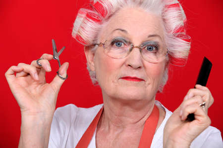 haircurlers: grandmother with scissors and haircurlers Stock Photo