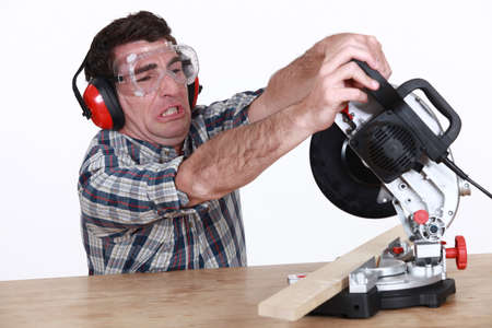 miter: Man struggling to use a mitre saw Stock Photo