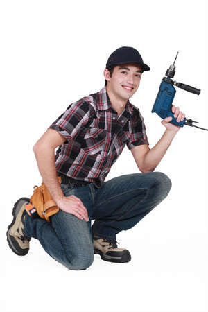 lain: Young manual worker kneeling with power drill
