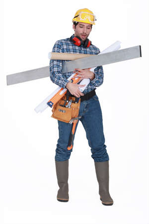 A construction worker with his arms loaded  photo