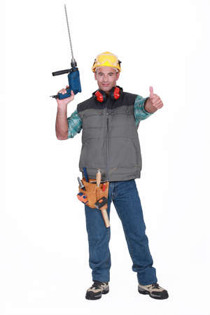 cordless: A handyman with a drill giving the thumb up