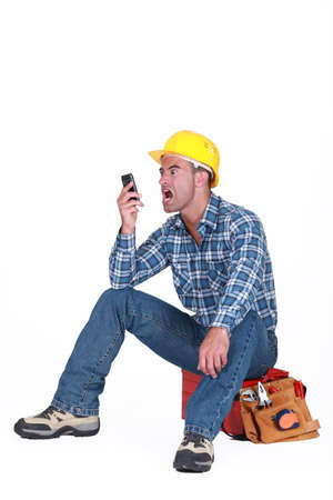 angry craftsman looking at his cell phone Stock Photo - 13459778