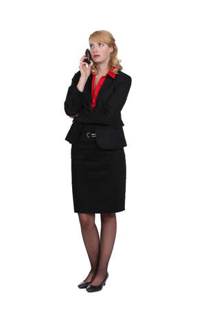 exasperated: Exasperated woman talking on her mobile phone Stock Photo