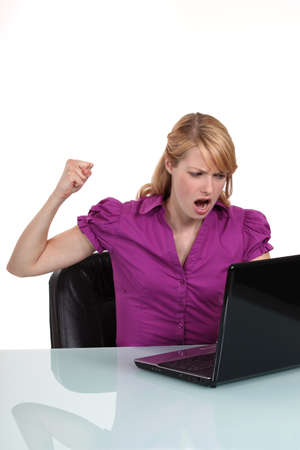aggressive people: Young woman angry with her laptop