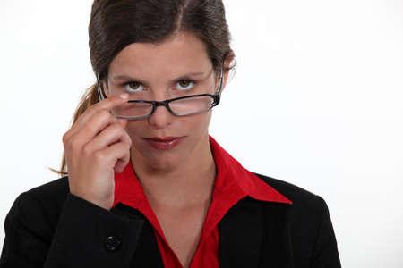 observant: Observant woman peering over her glasses Stock Photo