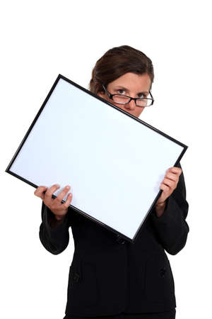 lowered: young secretary with glasses lowered holding white board