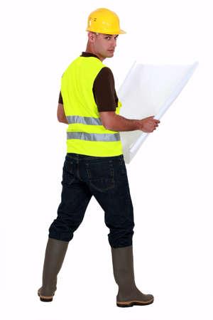 beine spreizen: Tradesman Blick auf eine Blaupause