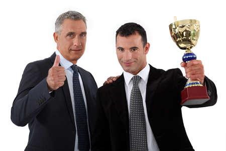 premios: Dos hombres de negocios que sostienen el trofeo