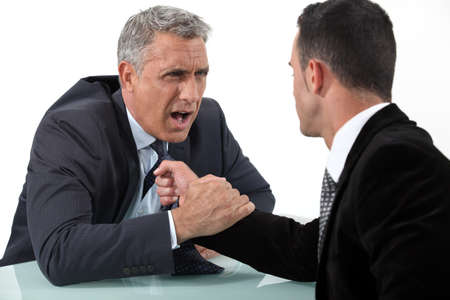 Businessmen fighting at desk photo