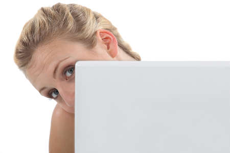 cagey: Woman peeking out from behind her laptop Stock Photo