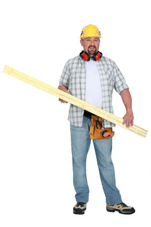 Tradesman carrying a plank of wood photo