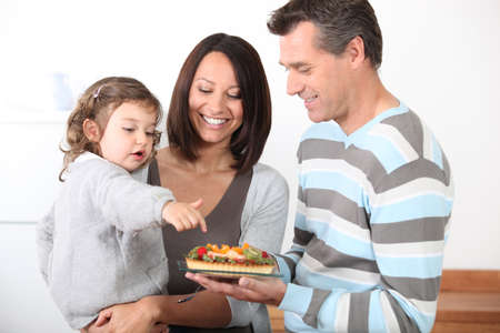 Parents preparing a bite to eat for little girl Stock Photo - 13459210
