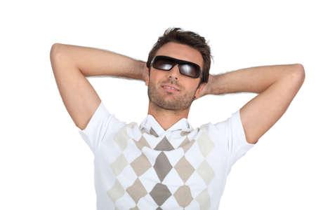 unconcerned: El hombre con gafas de sol con las manos detr�s de su cuello Foto de archivo