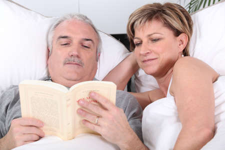 Middle-aged couple reading in bed photo