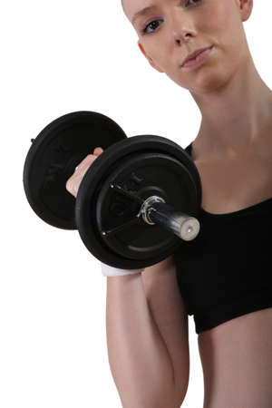 tiring: a young woman lifting a dumbbell