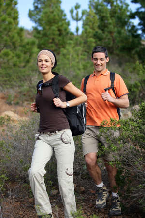 Young couple hiking through the woods photo