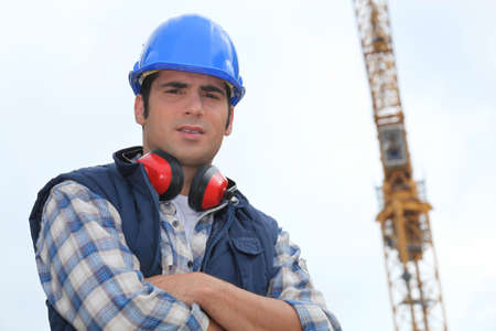Construction worker standing in front of a crane photo