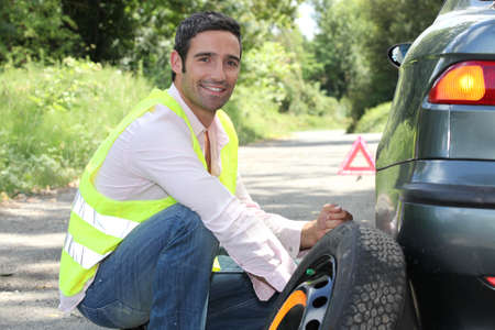 vest: Man changing a tyre