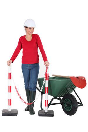 barrier island: Woman worker with a wheelbarrow and barrier