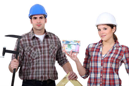 tradespeople: A team of tradespeople holding their tools and a house model