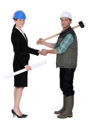 Businesswoman shaking the hand of a tradesman photo