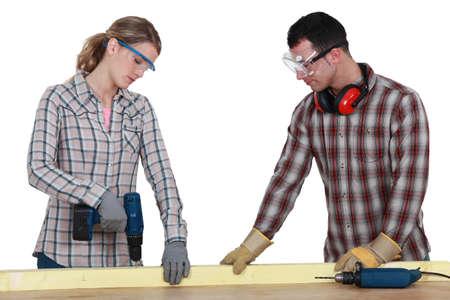 Couple drilling wood photo