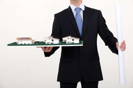 businessman holding an architectural model and a blueprint photo