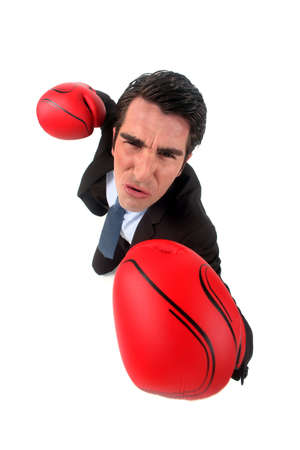 business challenge: businessman holding boxing gloves looking ferocious