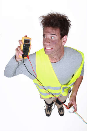 descarga electrica: electricista en probador de la celebración de una descarga Foto de archivo