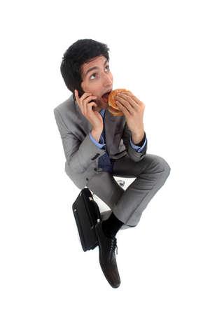 Businessman on the phone eating hamburger photo