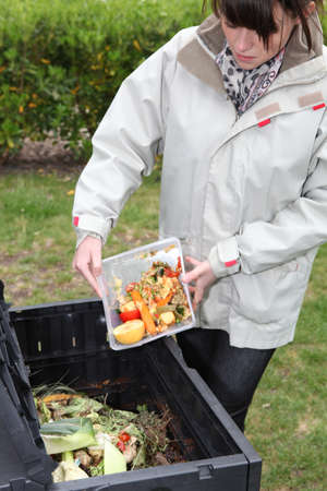 Woman making compost from old vegetables photo