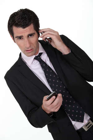 Businessman with two phones Stock Photo - 13457039