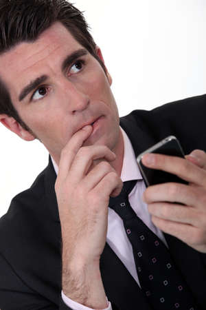 Anxious businessman with mobile phone photo