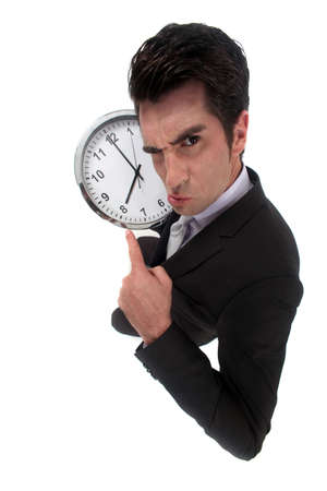 overburden: businessman pulling a face with clock Stock Photo