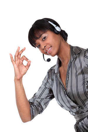 A businesswoman with a headset on making an ok sign  photo