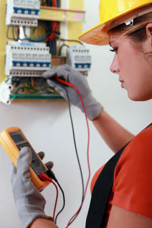 manual job: Female electrician checking the wiring on a fusebox Stock Photo
