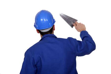 cemento: Trabajador que sostiene una paleta Foto de archivo