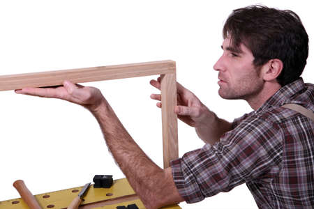 Joiner inspecting wooden frame photo
