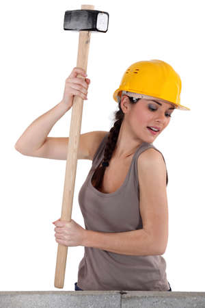 Tradeswoman using a mallet to hit stones photo