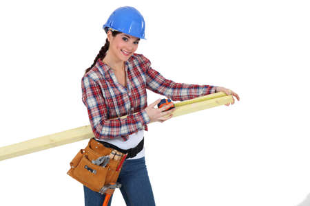 Female carpenter measuring a piece of wood  photo