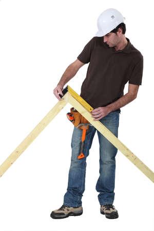 diligente: Trabajador con una regla de ángulo recto para medir un ángulo Foto de archivo