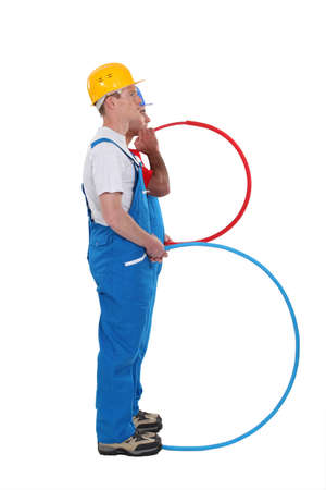 tradespeople: Construction workers standing side by side and holding tubes Stock Photo