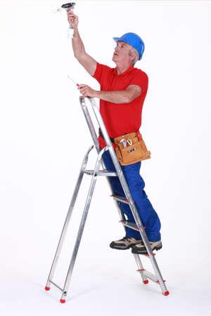 ladder safety: Tradesman installing a light fixture